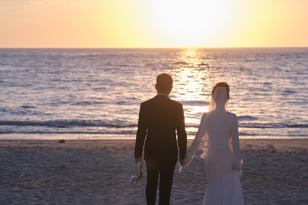 RANWEDDING仙台の沖縄ビーチプランで夕日を見つめる新郎新婦