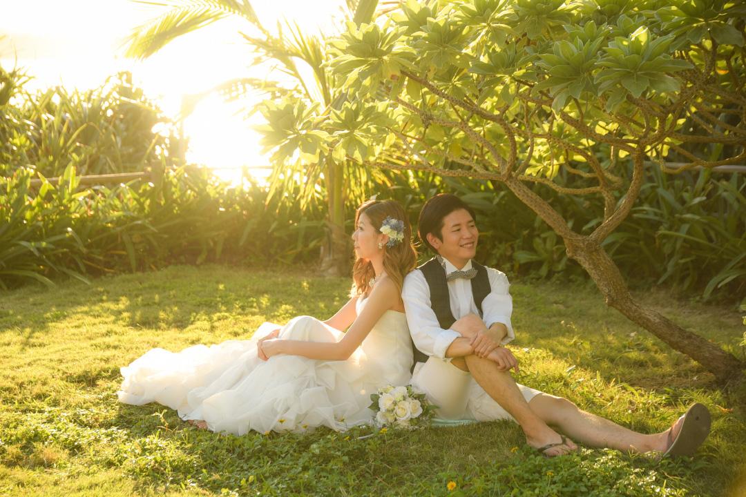 RANWEDDING仙台の沖縄チャペルプラン草原に座る新郎新婦